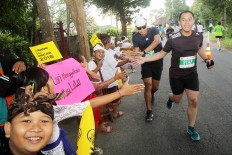 Young cheerleaders: Students from Klungkung village, Bali, cheer on runners on during the 2018 Maybank Bali Marathon on Sept. 9 as they approach the finish line.