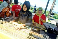 Women's empowerment: Anita, a female entrepreneur, weaves tenun (traditional woven cloth from Lombok, West Nusa Tenggara) in a showcase during the race pack collection for the 2018 Maybank Bali Marathon on Sept. 8 in Taman Bhagawan, Tanjung Benoa, Bali. Anita is one of the recipients of  Maybank Indonesia's women eco-weavers program, an initiative seeking to empower women through entrepreneurship, which the bank has been organizing since 2012.