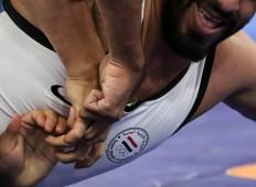 Yemeni wrestler Mohammed Almaghrebi tries to free himself during a match against Kyrgyzstani Ismailov Amantur. JP/Seto Wardhana