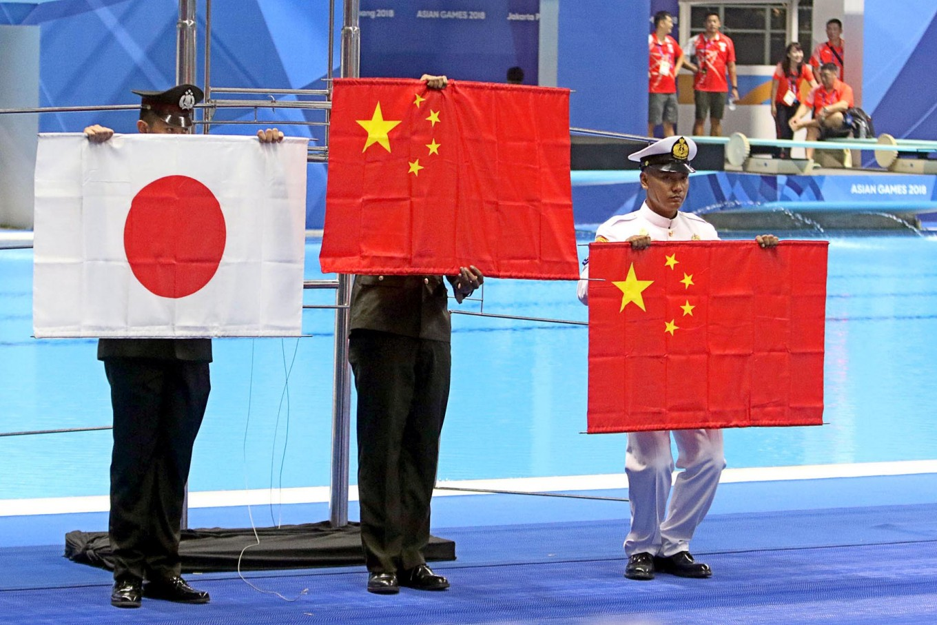 Officials hold the national flags of winning countries after they fell to the floor because of trouble with the flag pole. JP/Seto Wardhana