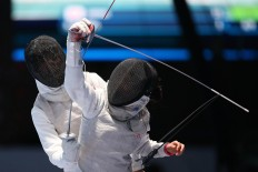 The sword of a Japanese fencer (front) gets tangled with a cable during women's team match against China. JP/PJ Leo