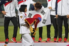A South Korean footballer teases a woman carrying the medals during a medal ceremony. South Korea's men's soccer team won over Japan's and secured the gold medal. JP/PJ Leo