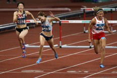 Indonesia's Emilia Nova (right) sprints in the women's 100-meter hurdles final and secures silver after South Korea's Jung Hye-lim Jung (center) finishes first.  JP/PJ Leo