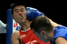 Indonesia's boxer Sunan Agung Amoragam takes a punch from Uzbekistan's Mirzakhalilov Mirazizbek in the men's boxing bantamweight semifinal. Sunan won the bronze after losing to Mirazizbek. JP/Seto Wardhana.