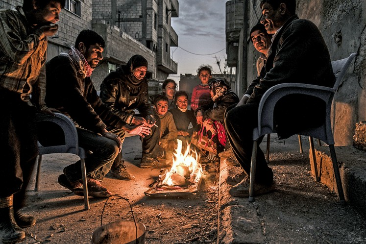Reality bites: Syrian Kurds gather around a fire in the city of Kobane. After the liberation, most houses were left without electricity or running water and food was also hard to find (March 2015).