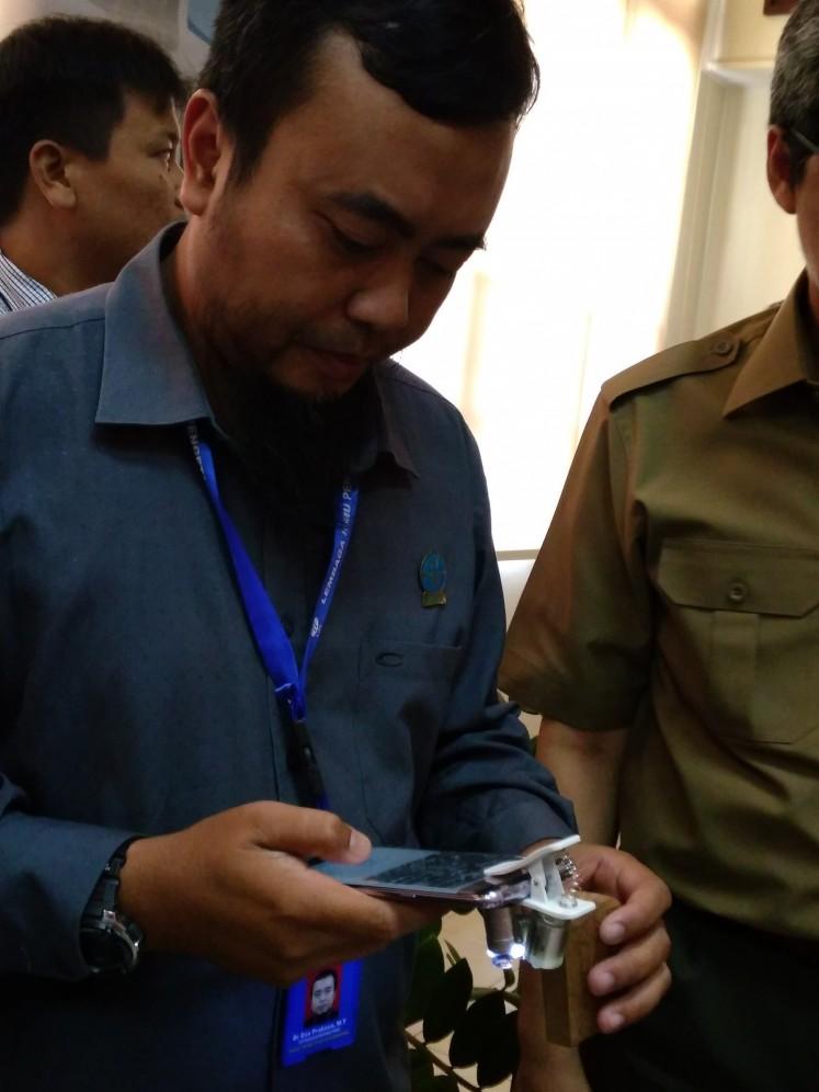 LIPI researcher Esa Prakasa demonstrates identifying a wood specimen with the AIKO app.