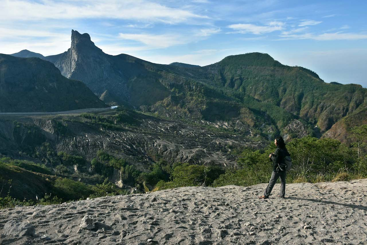 An observer looks at the slopes of Mount Kelud from afar.