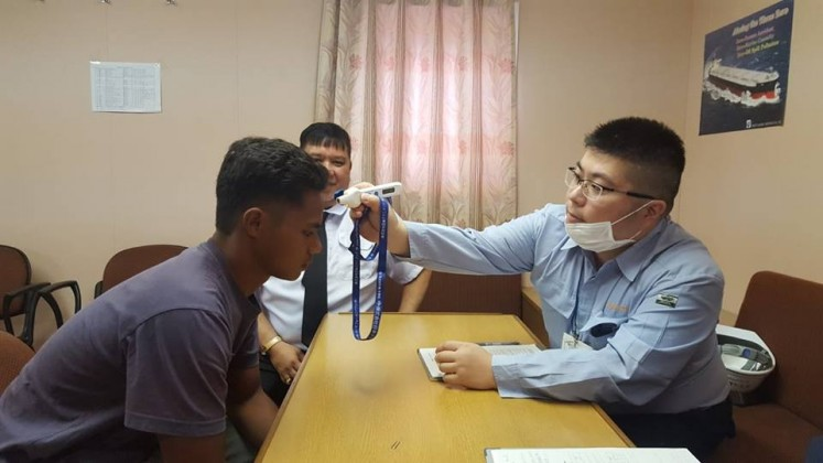 Aldi Novel Aldilang, 19, has his temperature taken by Japanese port authorities earlier this month. He was rescued after 49 days adrift in Guam waters.