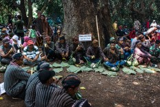 Villagers – clad in Javanese traditional costumes – sit on the ground under the shade of the trees of the Wonosadi forest. JP/Anggertimur Lanang Tinarbuko