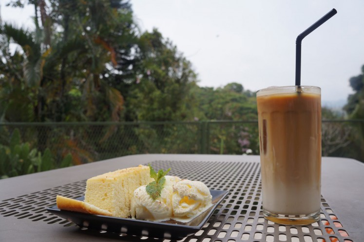 Visitors can enjoy lemon cake and iced latte with a mountainous view at Kiputih Satu cafe in Ciumbuleuit.