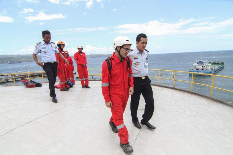Greenpeace activist from Malaysia Farhan Nasa (left) is escorted by immigration officials during the action in Bitung, North Sulawesi.