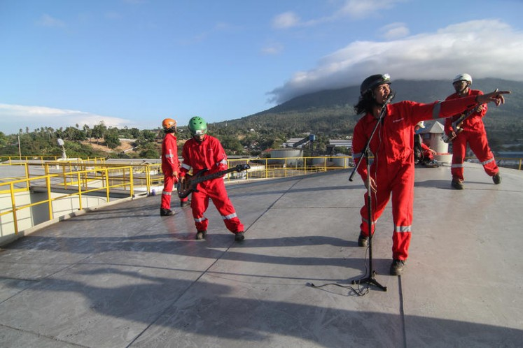 Indonesian rock band Boomerang performs on top of a silo at the Wilmar International refinery in Bitung, North Sulawesi.