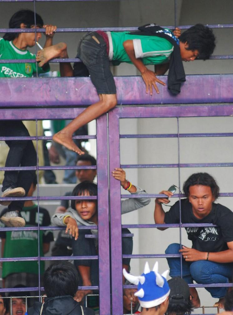 Supporters of Persebaya Surabaya, known as Bondo Nekat (Bonek), attempt to enter Jalak Harupat Stadium in Bandung, West Java, by climbing over the gate.
