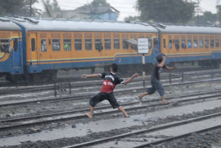 Two teenagers are seen throwing rocks at a Pasundan Train carrying Persebaya supporters at Purwosari Station in Surakarta, Central Java, on Jan. 24.