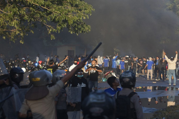 Supporters of PSIM Yogyakarta clash with the police during a second division match between PSIM Yogyakarta and PSS Sleman at Sultan Agung Stadium in Bantul, Yogyakarta, on July 26. The police are investigating the cause of the riot.