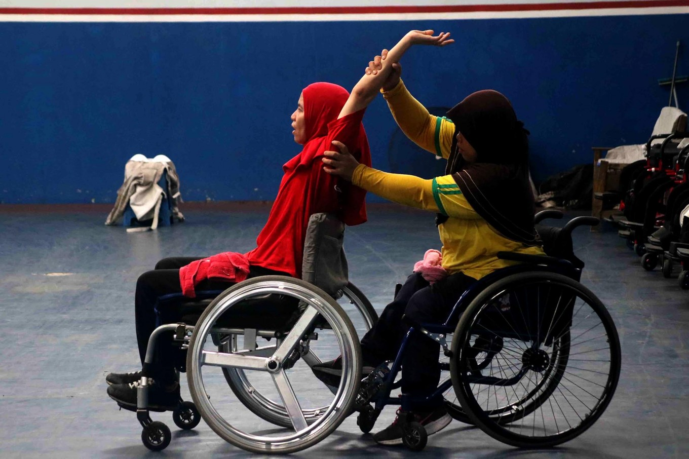 An athlete stretches, helped by her teammate, before the start of a training session. JP/Maksum Nur Fauzan