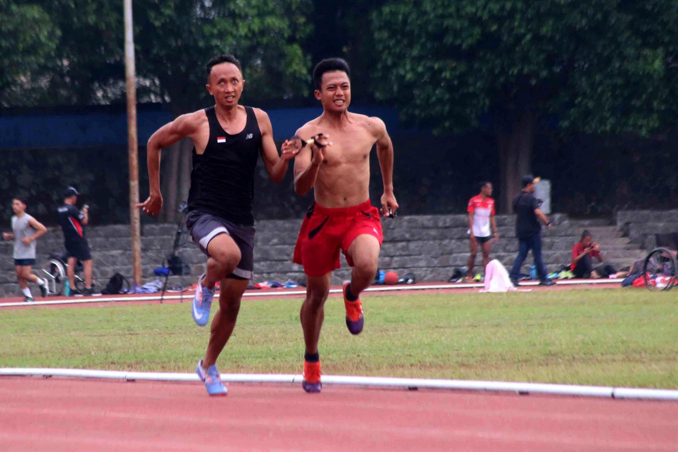 A visually impaired runner jogs alongside his chaperone during a training session. JP/Maksum Nur Fauzan]