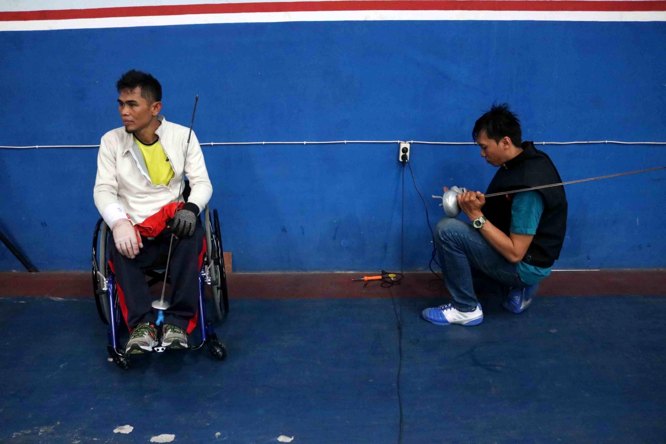 A wheelchair fencer waits for his sword to be fixed. JP/Maksum Nur Fauzan
