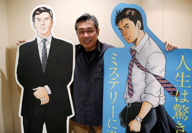 Kenshi Hirokane, the comic book author of the 'Kosaku Shima' and 'Like Shooting Stars in the Twilight' series, poses with cutouts of Kosaku Shima characters during an interview with Reuters at his studio in Tokyo, Japan September 10, 2018.