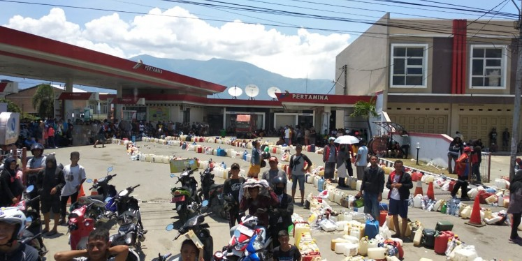 Survivors of an earthquake in Palu wait in line for fuel at a Pertamina gas station in the city on Oct. 1, 2018.