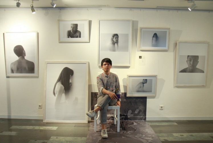 Yon Beni sits in front of his 'Revelare' photos at the 'Chrysalis' fashion photography exhibition on Thursday, Sept. 27 at Artotel Thamrin, Central Jakarta.