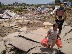 Residents salvage belongings after an earthquake and tsunami hit Palu on Sulawesi island on September 29, 2018.  Nearly 400 people were killed when a powerful quake sent a tsunami barrelling into the Indonesian island of Sulawesi, officials said on September 29, as hospitals struggled to cope with hundreds of injured and rescuers scrambled to reach the stricken region.  AFP/ Muhammad Rifki
