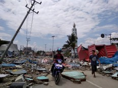 Residents make their way along a street full of debris after an earthquake and tsunami hit Palu, on Sulawesi island on September 29, 2018. Rescuers scrambled to reach tsunami-hit central Indonesia and assess the damage after a strong quake brought down several buildings and sent locals fleeing their homes for higher ground.   AFP/ Muhammad Rifki