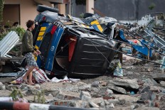 A man looks for belongings from his house after it was damaged in Palu in Central Sulawesi on September 29, 2018, following a strong earthquake and tsunami that struck the area. Nearly 400 people were killed when a powerful quake sent a tsunami barrelling into the Indonesian island of Sulawesi, officials said on September 29, as hospitals struggled to cope with hundreds of injured and rescuers scrambled to reach the stricken region. AFP/ Bay Ismoyo
