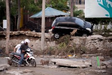 A man attempts to ride his motorcycle through the mud in Palu in Central Sulawesi on September 29, 2018, after a strong earthquake and tsunami struck the area. Nearly 400 people were killed when a powerful quake sent a tsunami barrelling into the Indonesian island of Sulawesi, officials said on September 29, as hospitals struggled to cope with hundreds of injured and rescuers scrambled to reach the stricken region.  AFP/ Bay Ismoyo