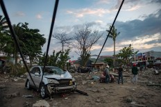 People view the damage to a beach hit by a tsunami in Palu in Central Sulawesi on September 29, 2018, after a strong earthquake and tsunami struck the area. Nearly 400 people were killed when a powerful quake sent a tsunami barrelling into the Indonesian island of Sulawesi, officials said on September 29, as hospitals struggled to cope with hundreds of injured and rescuers scrambled to reach the stricken region.  AFP/ Bay Ismoyo