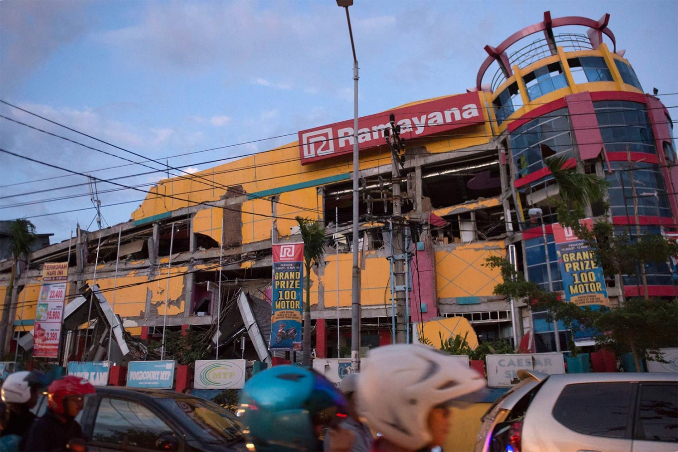 Motorists drive past a collapsed shopping mall in downtown Palu, Indonesia's Central Sulawesi on September 30, 2018, following the September 28 earthquake and tsunami. The death toll in Indonesia's quake-tsunami disaster nearly doubled to more than 800 on September 30, as ill-equipped rescuers struggled to reach scores of trapped victims, health officials resorted to mass burials and desperate residents looted shops for food and water. AFP/ Bay Ismoyo