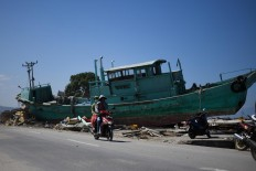 Earthquake survivors ride past a boat on a street in Palu, Indonesia's Central Sulawesi on October 1, 2018, after an earthquake and tsunami hit the area on September 28. The death toll from the Indonesian quake-tsunami nearly doubled to 832 but was expected to rise further after a disaster that has left the island of Sulawesi reeling. AFP/Jewel Samad
