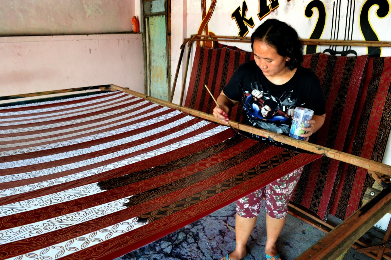 An artisan adds different colors to fabrics that have been stamped.