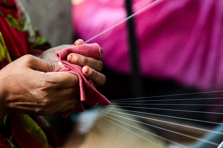 This photograph taken on September 5, 2018 shows a Bangladeshi worker making threads from boiled silk worm cocoons in a silk factory in Rajshahi.