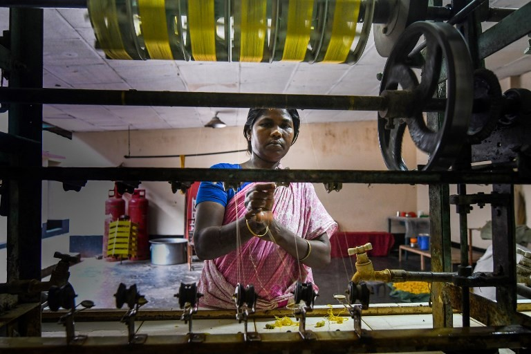 A Bangladeshi worker making threads from boiled silk worm cocoons in a silk factory in Rajshahi.
