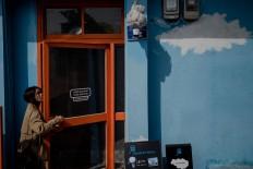 A woman enters a café. JP/Anggara Mahendra