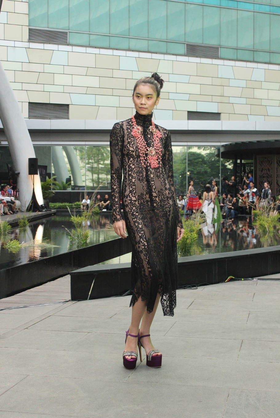 A model walks down the runway wearing an outfit designed by Billy Tjong during the Serenade of Tenun Doyo fashion show.