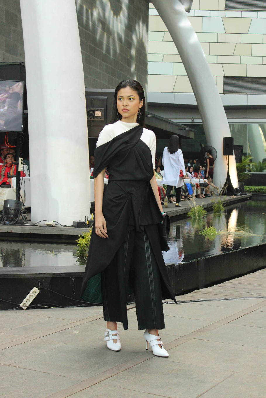 A model wears a black wrap dress from the Madeind x Billy Tjong ready to wear collection that can be purchased online.