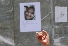 A survivor holds up a picture of a missing girl in Palu on Friday, October 5, 2018. JP/Dhoni Setiawan