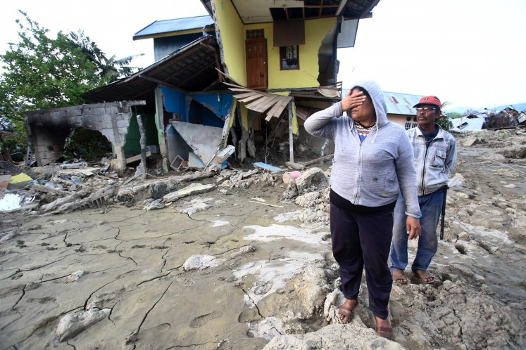 Survivors search for the exact location of their houses, which shifted as a result of soil liquefaction, in Petobo district, Palu, Central Sulawesi, on Oct. 3. Search and rescue teams are having difficulties in retrieving bodies buried in the mud.