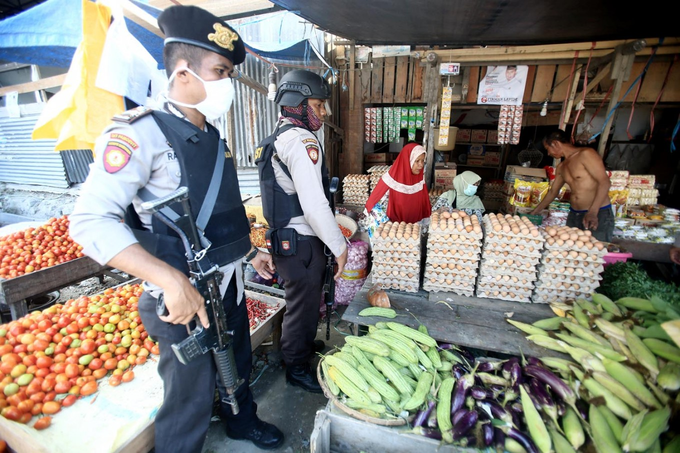 Police officers stand guard at the Masomba traditional market in Lolu subdistrict, South Palu, on Thursday, October 4, 2018. . Slowly, local economic activity has resumed in the city. JP/Dhoni Setiawan