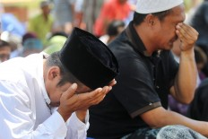 Two men weep after performing their Friday prayers in the front yard of the Darussalam Grand Mosque in Palu on Friday, October 5, 2018. The mosque was badly damaged by the strong earthquake and therefore religious activities are being conducted in the front yard, which also serves as a shelter for evacuees. JP/Dhoni Setiawan