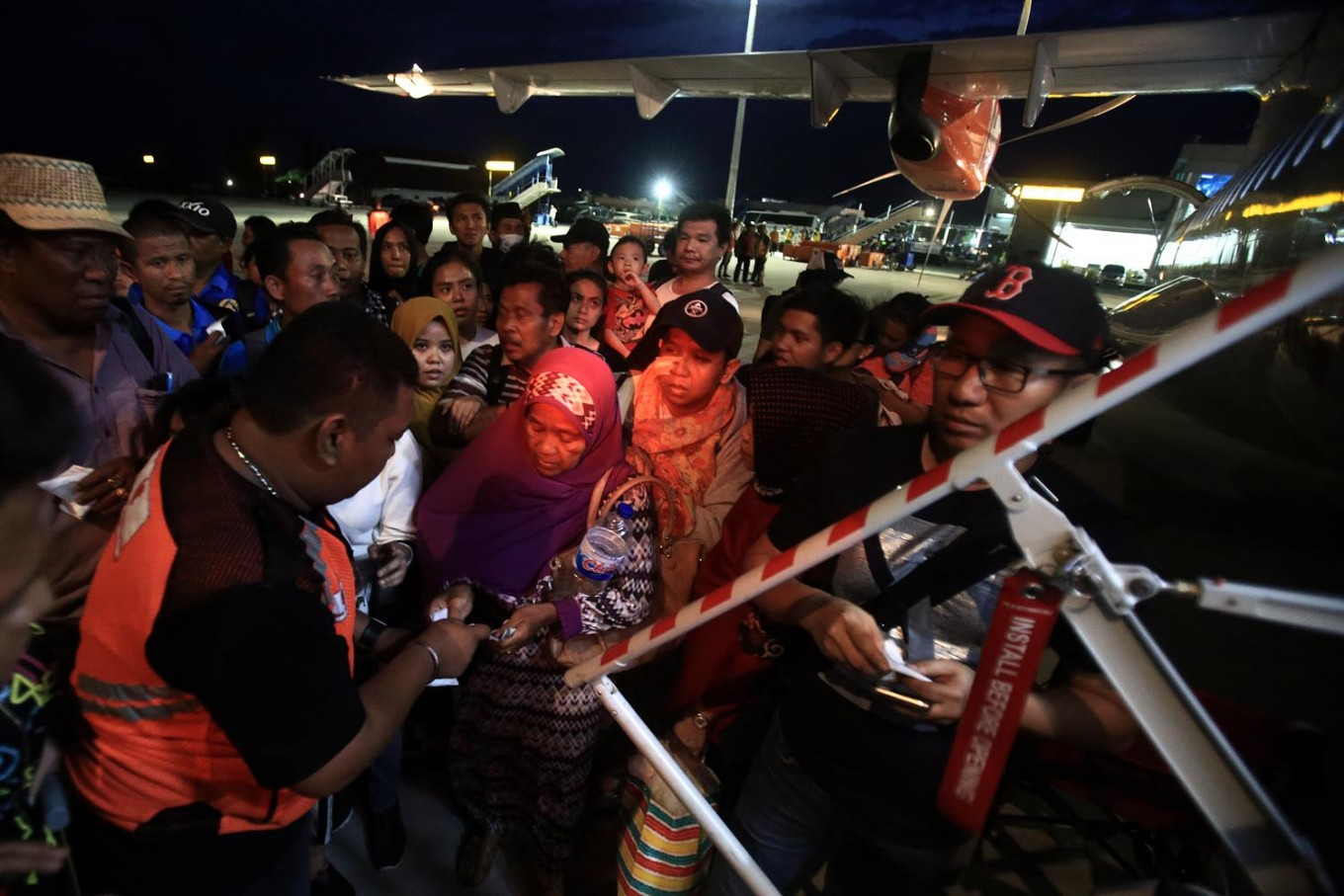 Survivors line up before boarding a military aircraft at the Mutiara SIS Al-Jufrie Airport in Palu, Central Sulawesi, on Tuesday, October 2, 2018. JP/Dhoni Setiawan