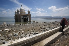 A survivor walks past the Arqam Baburahman Mosque at Talise Beach in Palu on Friday, October 5, 2018. The mosque was badly damaged in the quake and tsunami. JP/Dhoni Setiawan