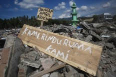 "Signs have been placed in the middle of the debris of tumbled houses. One of the signs reads ""Kami rindu ruma kami"" (we miss our home). JP/Dhoni Setiawan"