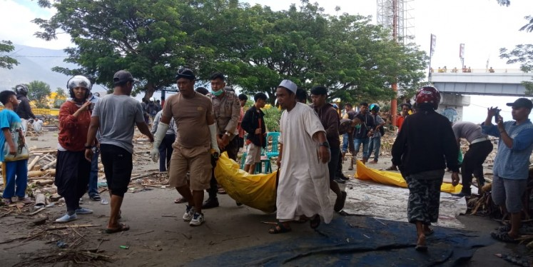 Survivors and police personnel retrieve bodies near Ponulele Bridge above Talise Bay in Palu city on Sept. 29, 2018.