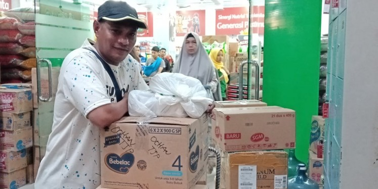 Ruslan Sangadji poses with aid supplies he bought in Makassar, South Sulawesi, on Friday (Oct. 5, 2018)
