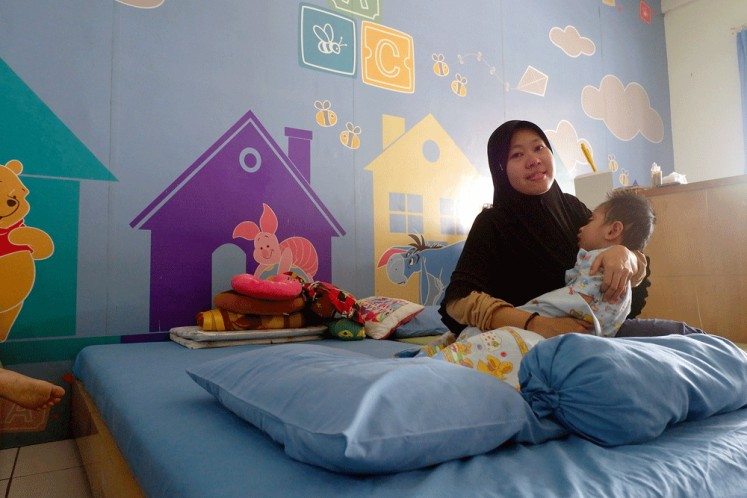Holding on: Hendri Handayani holds her baby, Arsyil Fadillah, who has been diagnosed with Anaplastic Ependymoma brain tumor.