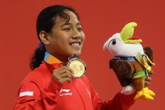 Moment of pride: Indonesian swimmer Syuci Indriani gives a salute after winning the gold medal in the 100-meter freestyle competition at the Gelora Bung Karno Aquatic Center in Senayan, Central Jakarta. INAPGOC/TJPimages/Hendra