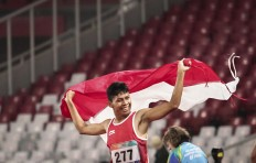 Victory lap: Indonesia's Sapto Yogo Purnomo raises the red and white flag of Indonesia after winning the gold medal in the 200-meter para-athletics event at the Gelora Bung Karno sports complex in Senayan, Central Jakarta. INAPGOC/TJPimages/Muhammad Bagas Syahputra